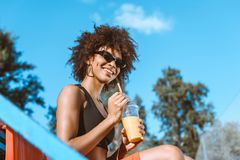 Free Young African-american Woman In Sports Bra Sitting In The Bleachers And Holding Royalty Free Stock Image - 118816536