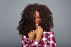 Young african american woman laughing with hair covering her face. Close up portrait of young african american woman laughing with hair covering her face stock photo