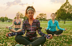 Young african-american woman leading a yoga class at sunset in nature park. Yoga fitness coach leading her group into a relaxing meditation with the sunlight Stock Photo