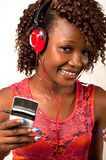 Young African American woman listening to music wi. Pretty young African American woman with headphones listening to music Stock Photos