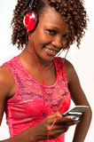 Young African American woman listening to music. Pretty young African American woman with headphones listening to music from her cellphone royalty free stock images