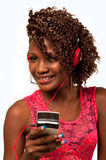 Young African American woman with headphones attac. Pretty young African American woman with headphones listening to music from a mobile phone royalty free stock image