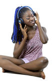 Young African American woman listening to music. Pretty young African American woman with headphones listening to music Royalty Free Stock Photo