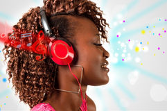 Young African American woman listening to music. Pretty young African American woman with headphones listening to music, glowing notes and lines concept royalty free stock image