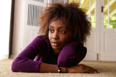 Young african american woman lying down looking away. Portrait of a young african american woman lying down on floor looking away Royalty Free Stock Photos