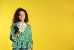 Young African-American woman with money on color background royalty free stock photo