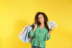 Young African-American woman with money and shopping bags stock images