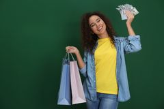 Young African-American woman with money and shopping bags on color background stock images