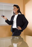 Young African-American woman in office texting Stock Images
