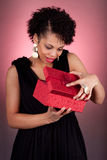 Young African American woman opening a gift. Portrait of a happy young African American woman opening a gift Stock Photo