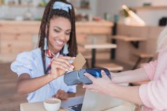 Young african american woman paying with credit card stock photography
