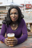 Young African American Woman Drinks Pint of Pale Ale Stock Photo