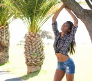 Young african american woman posing next to palm trees Royalty Free Stock Image