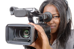 Young African American woman with professional video camera. A young African American woman with professional video camera and headphone Stock Photos