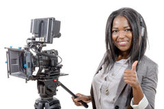 Young African American woman with professional video camera. A young African American woman with professional video camera and headphone Royalty Free Stock Image