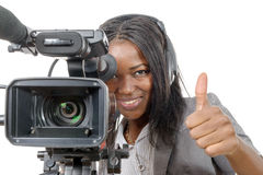 Young African American woman with professional video camera. A young African American woman with professional video camera and headphone Royalty Free Stock Photo