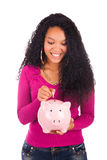 Young african american woman putting coin in piggy bank Stock Photos