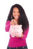 Young african american woman putting coin in piggy bank Stock Images