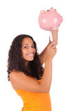 Young african american woman putting coin in piggy bank Royalty Free Stock Photos