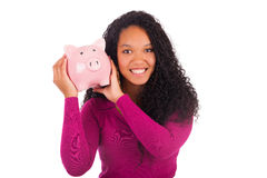 Young african american woman putting coin in piggy bank Royalty Free Stock Photography