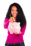 Young african american woman putting coin in piggy bank Stock Photography