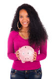 Young african american woman putting coin in piggy bank Royalty Free Stock Photo