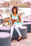 Young African American Woman reading book, relaxing by river in. Young African American woman wearing green tank top, blue fashionable jeans, sitting on deck at Stock Images