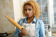 Young african american woman with rolling pin in the kitchen Royalty Free Stock Photo