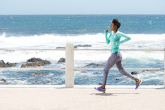 Young african american woman running by the sea Stock Image