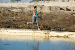 Young african american woman running by water Stock Photo