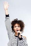 Young african american woman singing with microphone isolated on grey Royalty Free Stock Photo