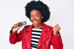 Free Young African American Woman Singing Song Using Microphone Screaming Proud, Celebrating Victory And Success Very Excited With Stock Image - 212166671