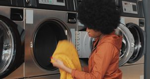 Young African American woman sits in front of a washing machine and take away laundry clothes. Self-service public stock video footage