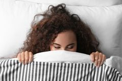 Young African-American woman sleeping on soft pillow, top view. Bedtime stock photography