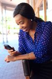 Young african american woman smiling with mobile phone Royalty Free Stock Photography