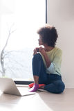 Black woman in the living room on the floor. Young african american woman smiling sitting on the floor near bright window while looking at open laptop computer Stock Image