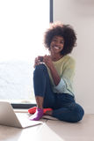 Black woman in the living room on the floor. Young african american woman smiling sitting on the floor near bright window while looking at open laptop computer Royalty Free Stock Photos