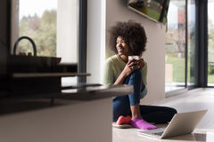 Black woman in the living room on the floor. Young african american woman smiling sitting on the floor near bright window while looking at open laptop computer Stock Photo