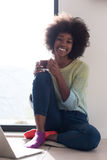 Black woman in the living room on the floor. Young african american woman smiling sitting on the floor near bright window while looking at open laptop computer Royalty Free Stock Photo