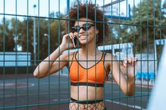 Young african-american woman in sportive attire and sunglasses talking on smartphone behind. Wired fencing Royalty Free Stock Images