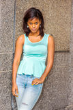 Young African American Woman thinking outside in New York. Young African American woman wearing green tank top, fashionable jeans, drop earrings, standing royalty free stock images