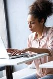 Young african american woman typing on laptop Stock Images