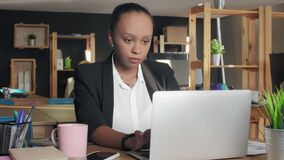 Young african american woman typing on laptop in office