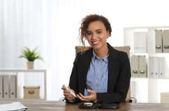 Young African-American woman using lancet pen at workplace. Diabetes control royalty free stock images