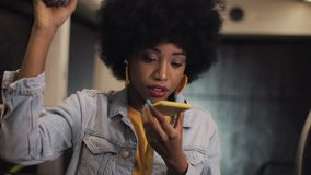 Young african american woman using smart phone voice recognition, dictates thoughts, voice dialing message riding in the