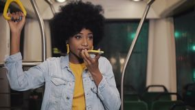 Young african american woman using smart phone voice recognition, dictates thoughts, voice dialing message riding in the. Public transport stock footage