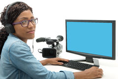 Young African American woman video editor. With computer and camcorder stock photography