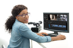 Young African American woman video editor. With computer and camcorder stock images