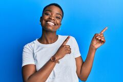 Free Young African American Woman Wearing Casual White T Shirt Smiling And Looking At The Camera Pointing With Two Hands And Fingers To Stock Images - 217578624