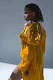 Young african american woman in wet yellow raincoat posing in studio. Beautiful young african american woman in wet yellow raincoat posing in studio Stock Image